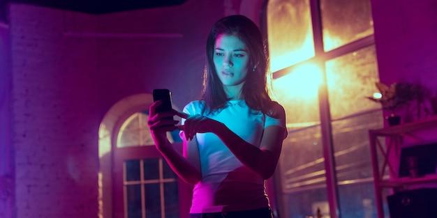 궁금하다. 네온 조명이 켜진 실내에서 잘생긴 세련된 여성의 영화적 초상화. 보라색 - 파란색의 영화 효과처럼 톤. 실내에서 화려한 조명으로 스마트폰을 사용하는 백인 여성 모델. 전단.