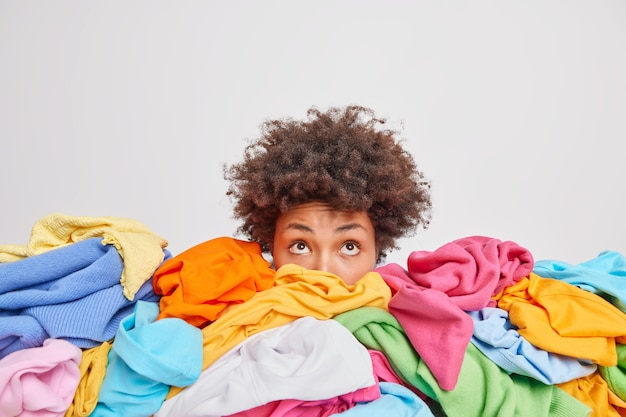 Wondered curly haired ethnic woman focused above surrounded by multicolored laundry cluttered with clothes collects clothing for recycling isolated over white wall. organize your closet