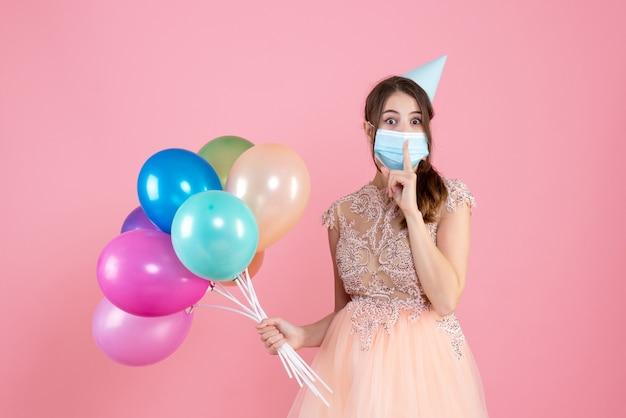 Si chiedeva ragazza con cappello da festa e maschera medica facendo segno shh con palloncini colorati su rosa