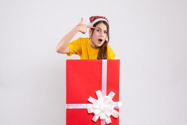 흰색에 큰 크리스마스 선물 뒤에 서있는 그녀의 사원에 손가락 총을 유지하는 산타 모자와 궁금 소녀