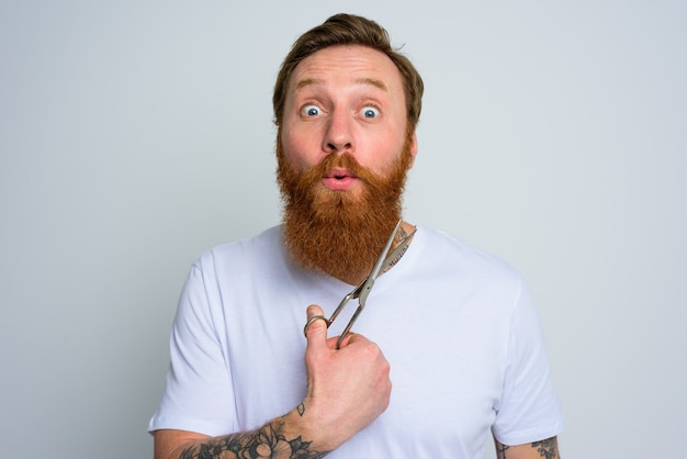 Wondered man with scissors is ready to cut the beard