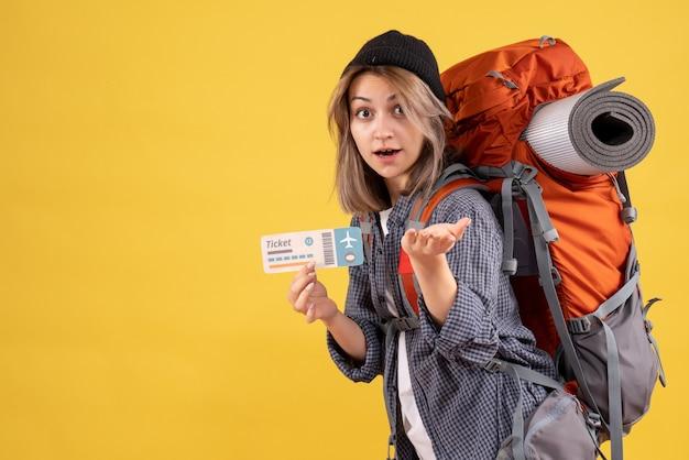 チケットを保持しているバックパックを持つ不思議な旅行者の女性