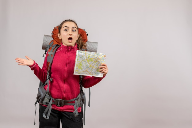 灰色の地図を持った大きなバックパックを持った旅行者は不思議に思った