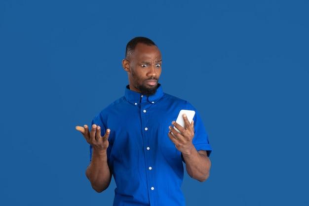 전화 사용이 궁금합니다. 파란색 벽에 고립 된 젊은 아프리카 계 미국인 남자의 흑백 초상화.