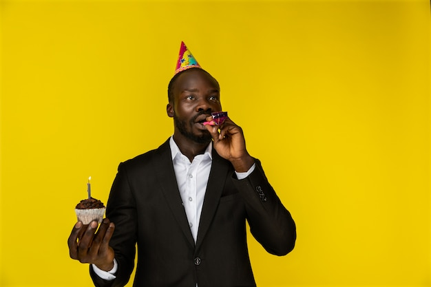 Wondered young afroamerican guy in black suit and birthday hat with burning candle on the cupcake