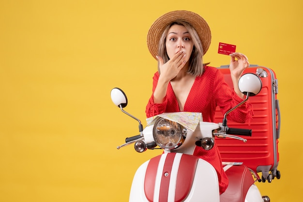 Удивилась молодая женщина в красном платье с кредитной картой возле мопеда