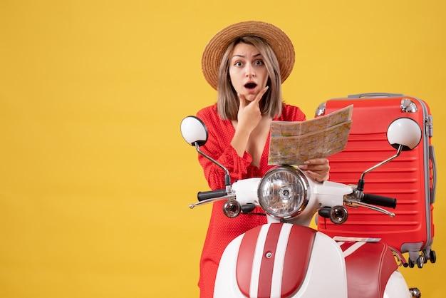 モペットの近くのあごに手を置いて地図を持っている赤いドレスを着た若い女性が不思議に思った