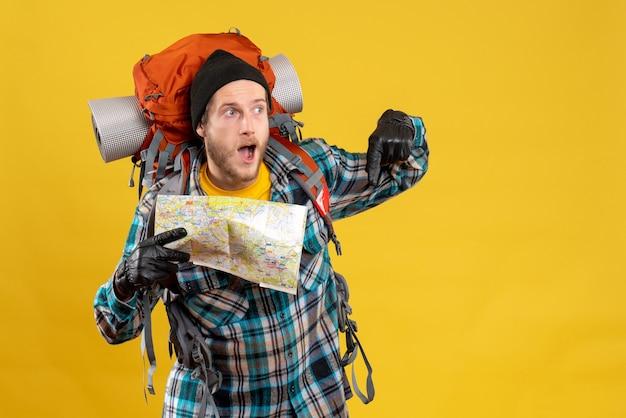 Удивился молодой турист с кожаными перчатками и рюкзаком, держащий карту, указывающую на пол