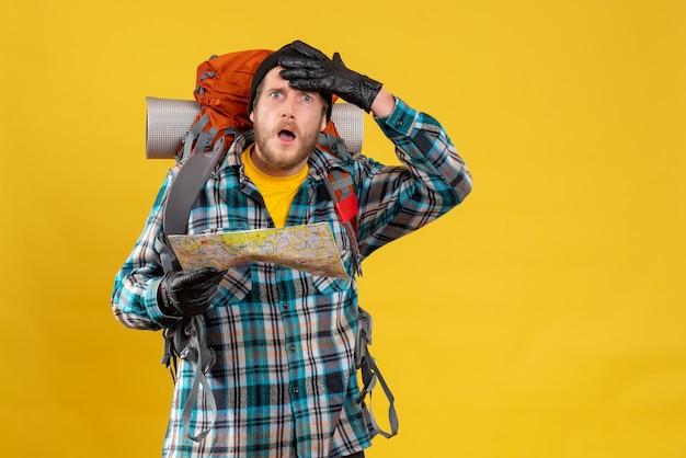 革の手袋と旅行地図を持ったバックパックを持った若い観光客は不思議に思った