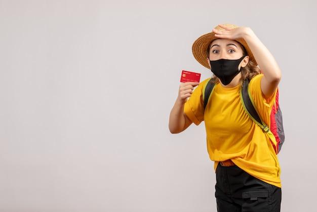 화이트 카드를 들고 검은 마스크 궁금해 젊은 여자