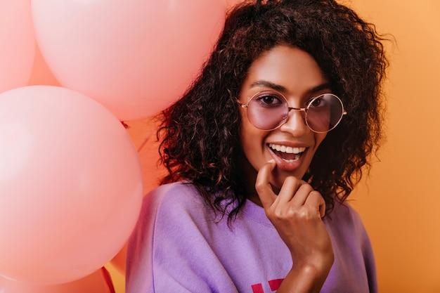 Meravigliosa signora africana giocosamente in posa con palloncini festa. affascinante ragazza dai capelli scuri con gli occhiali che celebra il compleanno.