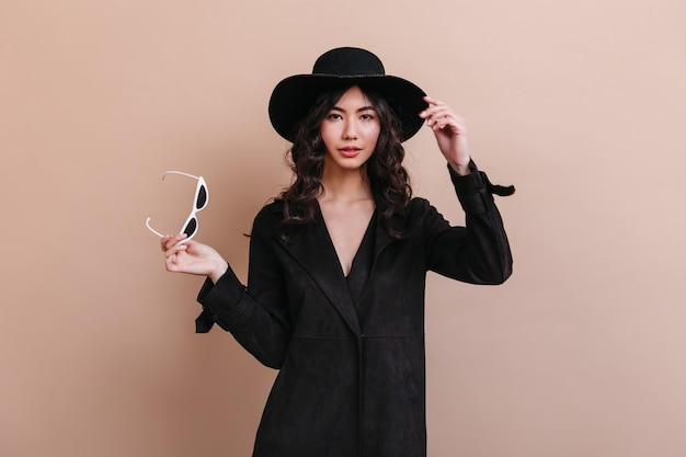 Wonderful asian woman in coat holding sunglasses. front view of well-dressed korean woman isolated on beige background.