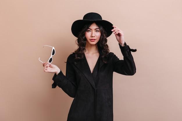 サングラスを保持しているコートの素晴らしいアジアの女性。ベージュの背景で隔離の身なりのよい韓国人女性の正面図。