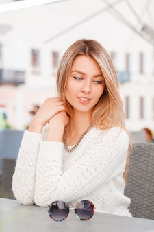 파란 눈을 가진 니트 빈티지 니트 스웨터에 멋진 아름 다운 젊은 여자가 앉아서 화창한 날 여름 야외 카페에서 꿈을 꾸고 있습니다. 매력적인 소녀는 나머지를 즐깁니다.