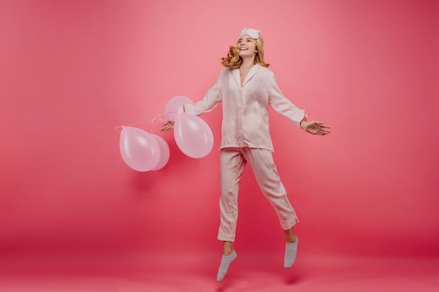 아침에 점프하는 귀여운 양말에 멋진 생일 소녀. 파티 전에 장난 꾸러기 잠옷에 흥분된 여성 모델의 전체 길이 실내 사진.