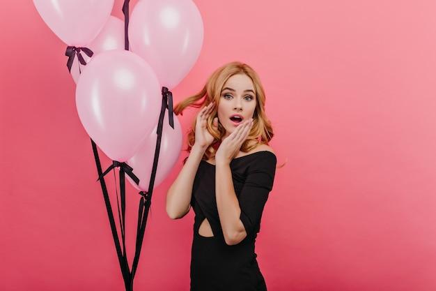 놀라움을 표현하는 트렌디 한 메이크업으로 멋진 생일 소녀. 밝은 분홍색 벽에 포즈 금발 머리와 놀된 예쁜 여자의 실내 사진.