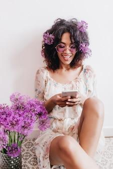 笑顔で素晴らしい黒のブルネットの女性のテキストメッセージメッセージ。ネギの花束の横に座っているかわいいアフリカの女の子の屋内ショット。