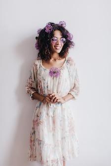 꽃과 흰 벽 앞에 서있는 멋진 흑인 여성 모델. 보라색 마늘 류를 들고 행복 한 아프리카 여자