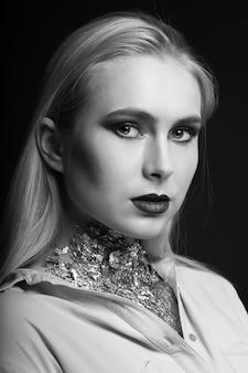 彼女の首に明るい化粧とホイルでスタジオでポーズをとっている素晴らしいブロンドのモデル。モノクロショット