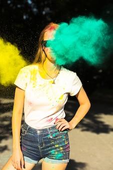 色のホーリー祭を祝うサングラスの素晴らしいブロンドの女性