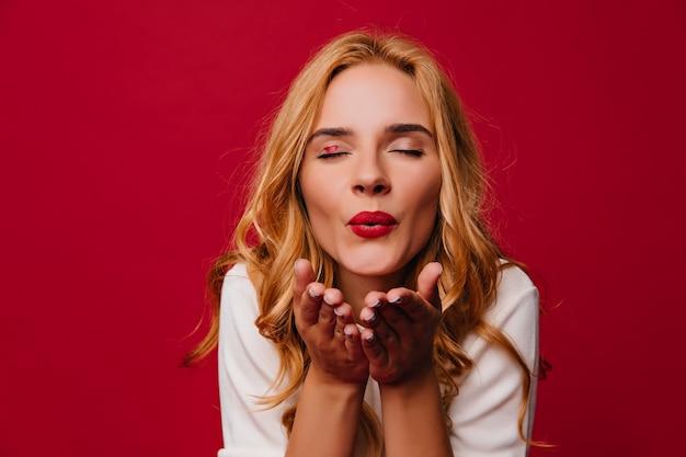 空気のキスを送る素晴らしいブロンドの女性。赤い壁にポーズをとる愛らしい愛らしい女の子。