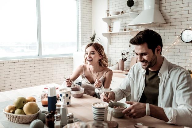 멋진 아침 식사. 흰 셔츠에 젊은 장발 예쁜 여자와 그녀의 남편이 함께 아침 식사를하는 동안 놀라운 느낌