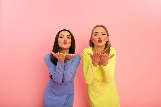 黄色と青の夏のスタイリッシュなドレスを着た素晴らしい明るい女性。大きな赤い唇とモダンな髪型の金髪とブルネット。形の良い熱い体、セクシーなモデル。ピンの背景にスタジオで撮影