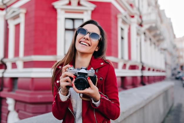 Meravigliosa donna bianca dai capelli castani che ride mentre posa con la fotocamera