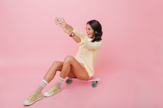ピンクのインテリアの部屋でスケートボードに座っている黄色の衣装で素晴らしいブルネットの女性。セルフィーを作るかわいい靴下で夢のような女の子の屋内肖像画。
