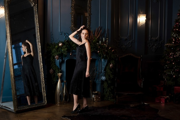 큰 거울이 있는 디자이너 장식된 방에서 포즈를 취한 멋진 브루네트 여성