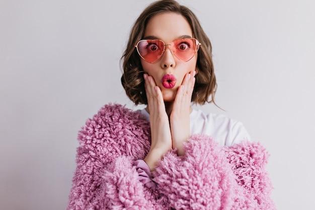 光の壁に驚きの感情を表現する素晴らしい白人の女の子。ピンクの毛皮のコートとサングラスで恍惚とした驚いた女性の写真。