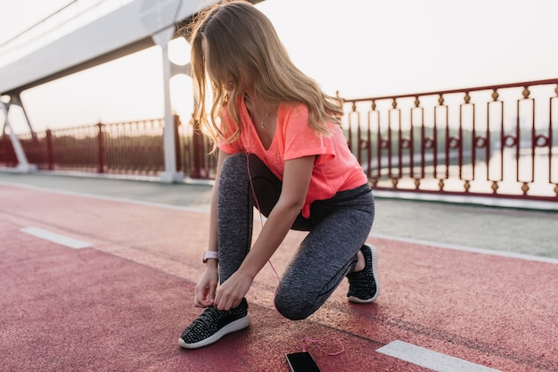 Wonderful caucasian lady in earphones ties up her shoelaces at stadium. outdoor shot of cute girl sitting at cinder track and listening music.