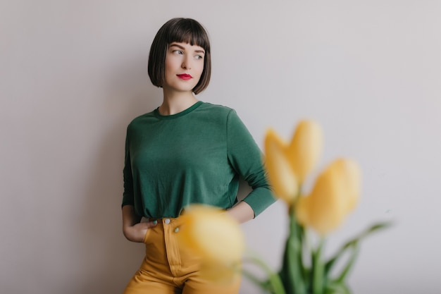 Wonderful caucasian woman with dark hair standing near wall and looking away. indoor photo of elegant female model with yellow flowers on foreground.