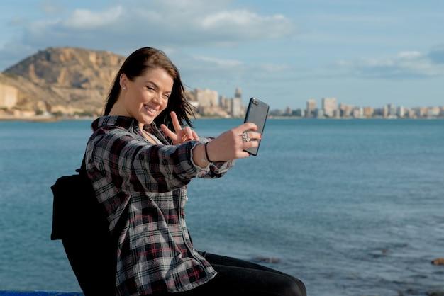 素敵な陽気な若い女性旅行者が屋外で楽しくポーズをとる晴れた日に彼女の携帯電話で自画像を作成します