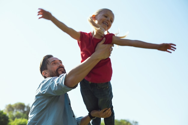 Wonderful childhood. alert bearded father smiling while having fun with his little daughter
