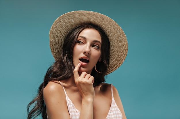 Meravigliosa bruna riccia con cappello di paglia elegante a tesa larga e top scozzese che guarda lontano e flirta sulla parete blu