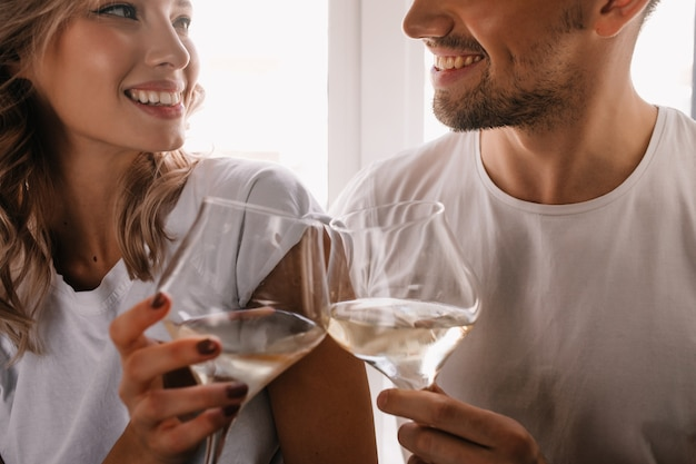 Wonderful curly woman celebrating anniversary with boyfriend. couple drinking champagne.