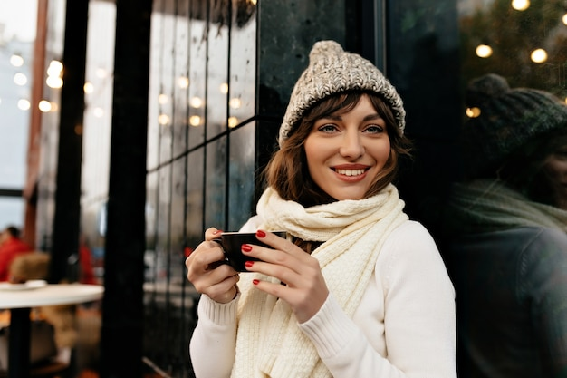 ニット帽とセーターを着てコーヒーとカップを持ち、外でコーヒーブレイクを楽しんでいる素敵な笑顔の素敵なかわいい女性。高品質の写真