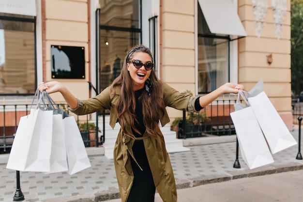 Meravigliosa modella dai capelli scuri che si diverte per strada e sventola le borse del negozio