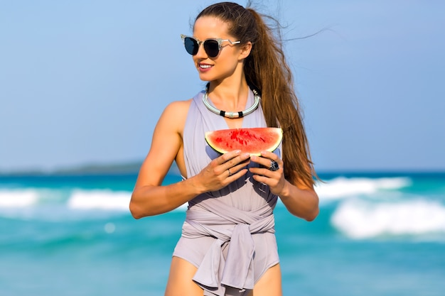 夏休みに海リゾートでポーズのサングラスで素晴らしい黒髪の少女。スイカを押しながら海を背景に離れているブルネットの女性モデルの屋外のポートレート。
