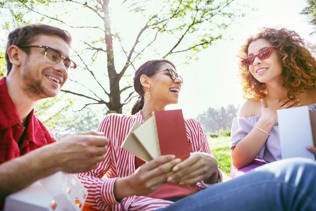 멋진 하루. 동료와 함께 야외에 앉아 시작에 대해 논의하는 활기 넘치는 검은 머리의 여성