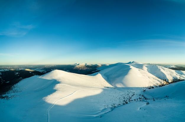 Замечательная дневная панорама сугробов в горах среди лесов в солнечный морозный туманный день. концепция первозданной природы северной природы