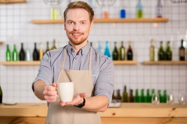 素晴らしい飲み物。カフェでウェイターとして働いている間、笑顔であなたにお茶を提供している陽気な素敵なひげを生やした男