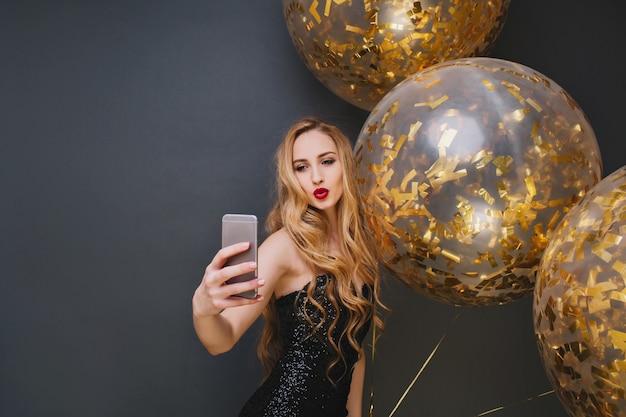 키스 얼굴 표정으로 셀카를 만드는 멋진 유럽 소녀. 큰 풍선과 함께 생일 파티를 즐기는 긴 머리를 가진 웅장한 젊은 여자.