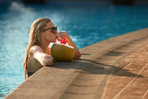 Wonderful female tourist with blond hair relaxing in pool with clear blue water and drinking coconut from straw. young lady in sunglasses and swimwear spending sunny days in water