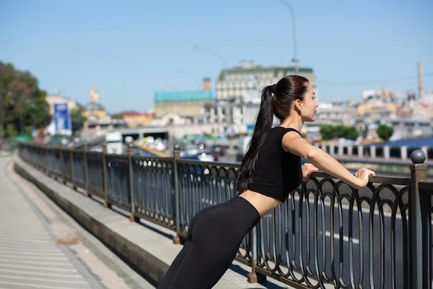 通りで運動をしているスポーツ服を着ている素晴らしいフィットネス女性。テキスト用のスペース