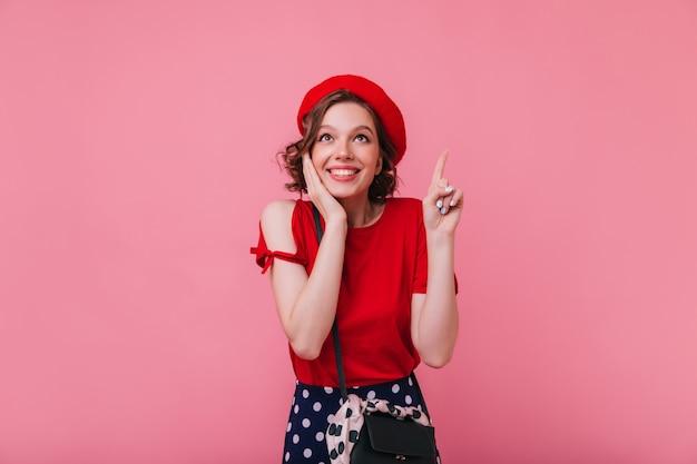 놀란 미소로 포즈를 취하는 물결 모양의 헤어 스타일로 멋진 프랑스 소녀. 고립 된 빨간 베 레 모에 우아한 백인 여자의 실내 사진.