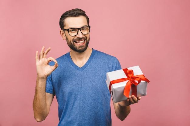 素敵なプレゼント!彼の誕生日プレゼントボックスokサインを持って美しい笑顔で魅力的な男の愛らしい写真。