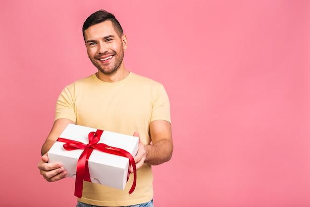Замечательный подарок привлекательный мужчина с красивой улыбкой держит коробку для подарка на день рождения