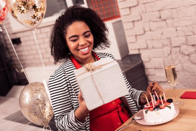 Замечательный подарок. радостная позитивная женщина улыбается, глядя на настоящее